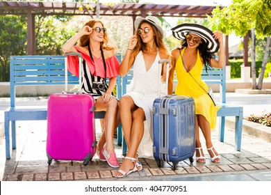 Three beautiful fashion girls sitting with their suitcases and wait in the terminal at the airport. Blonde, redhead, brunette, dressed in bright dresses and hats.