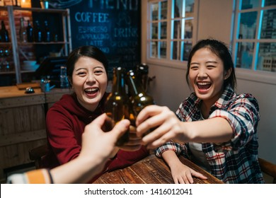 three beautiful female friends clinking bottles of beer and smiling while resting at night pub. group of happy young people cheers celebrating cheerful laughing sitting in late midnight dark bar.
