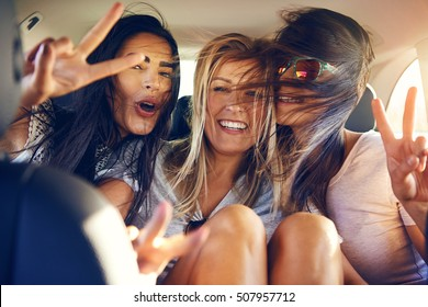 Three beautiful female friends make peace signs while seated in back seat of car with wind in their hair