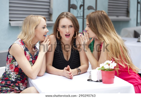 Three beautiful girlfriends gossiping woman sitting in the summer city cafe