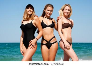 Three beautiful girlfriends having fun on the beach