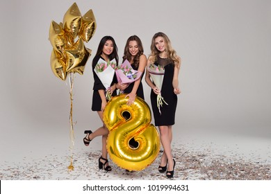 Three beautiful girls in black dresses are holding tulip bouquets. Eight-shaped big balloon. Confetti. Happy woman's day