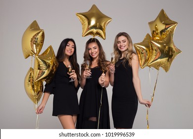 Three beautiful girls in black dresses are holding wineglasses with champagne. Star-shaped balloons.  Happy woman's day