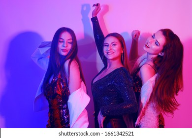 Three beautiful girls are dancing in neon. An incredibly fun party with girls in shiny dresses, they celebrate the holiday, smile, laugh, dance, sing. Night club dancing.