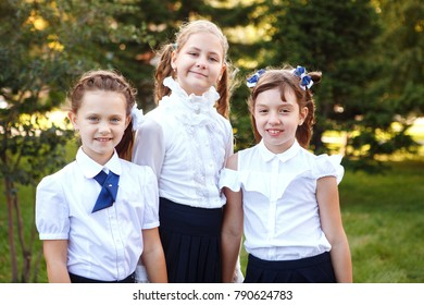 Three beautiful girls of elementary school pupils in uniform in the Park