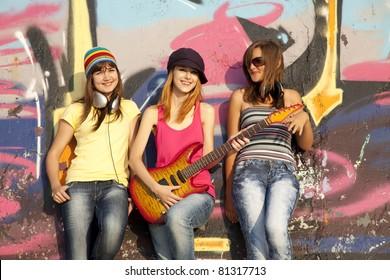Three beautiful girls with guitar and graffiti wall at background.