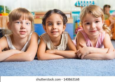 Three beautiful girls lying on floor at daycare