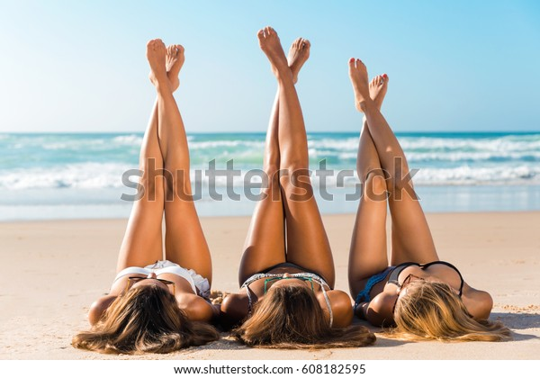 Three beautiful girls on the beach lying on the sand