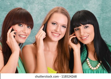 three beautiful girls  on a green with a mobile phone
