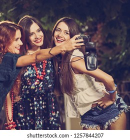 Three beautiful girls smiling while making selfie, image with warm vintage toning and square aspect ratio