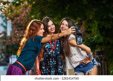 Three beautiful girls smiling while making selfie