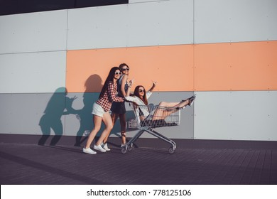 three beautiful girls in sunglasses have fun in the grocery cart under the supermarket in the summer