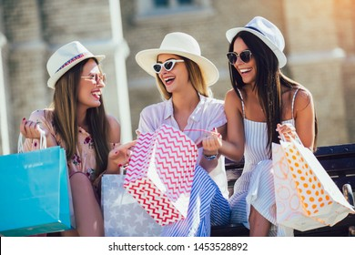 Three beautiful girls in sunglasses with shopping bags in city.
