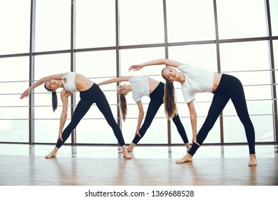Three beautiful girls in a yoga studio. Women make exercise in a gym