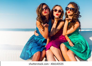 Three  beautiful   glamour  girls  in same colorful dresses posing near the beach, wearing stylish sunglasses and enjoying vacation in summer city. Bright colors. Casual outfit. Send kiss.