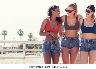 Three beautiful multi ethnic smiling girlfriends posing together.Sunny summer day at italian coast. Group of women with fit bodies wearing fashionable sunglasses and short jeans. Vacation time.