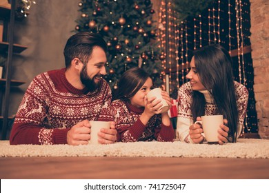 Three beautiful relatives at home, adorable charming girl with mom and dad, in knitted cute traditional x mas costumes, having cups of  coffee, chocolate, milk to warm-up, celebrate, holiday