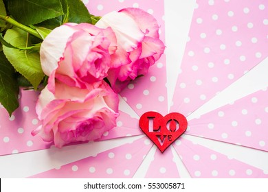 Three beautiful roses and red wooden figure of heart on pink and white background. St. Valentine's day