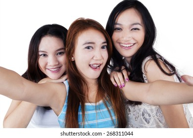 Three beautiful schoolgirls taking self photo together, isolated on white background