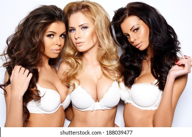 Three beautiful sexy curvaceous young women modeling white bras showing off their ample cleavages as they pose arm in arm looking seductively at the camera