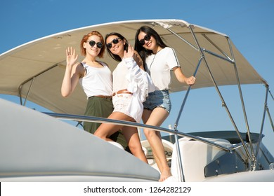 Three beautiful and slender girls posing and standing on yacht. Charming women smiling and looking at camera. Two brunettes and one woman with ginger hair wearing white clothes and sunglasses.