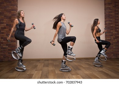 Three beautiful and sport girl in the gym training. Kangoo jumping. Beautiful girls in Kangoo Jumping training in the gym