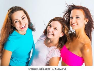 three beautiful teenage girls smiling on light background