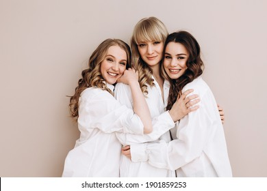 three beautiful women of European appearance hug and smile on a pink background. Several ladies in white shirts. Female friendship. High quality photo