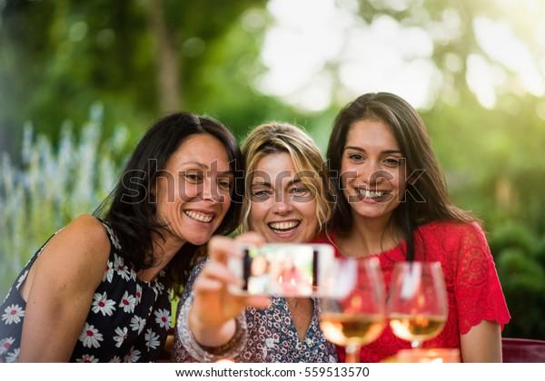 Drei schöne Frauen, die sich bei einer Selbstbedienung auf der Terrasse am Sommerabend amüsieren