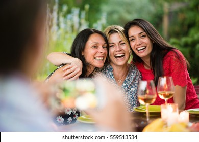 Three beautiful women posing for a photo around a terrace table by a summer evening