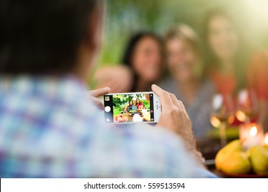 Three beautiful women posing for a photo around a terrace table by a summer evening. Focus on the smartphone. Shot with flare