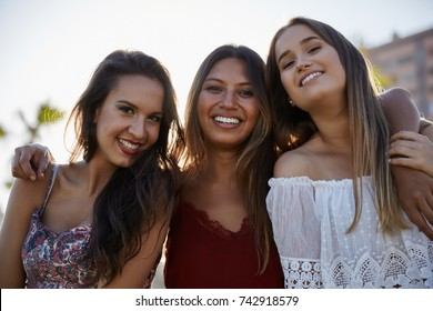 Three beautiful women standing together smiling