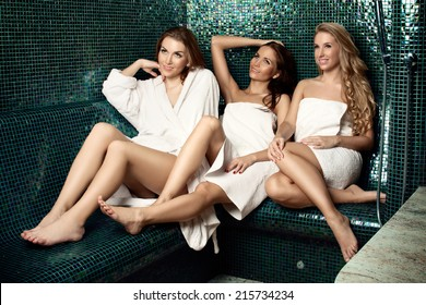 Three beautiful women in a white bathrobe and in a white towels sitting in  a sauna 4ed105ba8