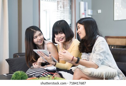 Three beautiful young asian women friends using tablet computer talking smiling and laughing together