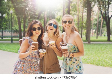 Three beautiful young boho chic stylish girls portrait in park. Happy smiling friends in colored sunglasses, having fun outdoors. Attractive young women drink coffee in summer city, youth fashion