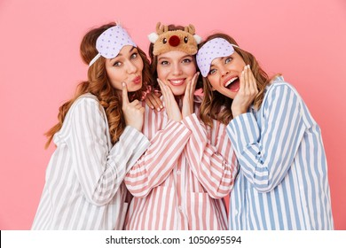 Three beautiful young girls 20s wearing colorful striped pyjamas and sleeping masks having fun during girlish sleepover isolated over pink background