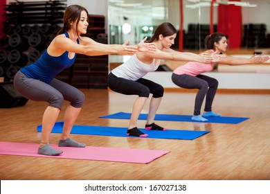 Three beautiful young women doing some squats and exercising at a gym
