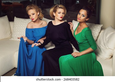 Three beautiful young women in evening gowns sitting on creamy sofa