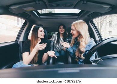Three beautiful young women friends have fun in the o car as they go on a road trip together for their summer vacation
