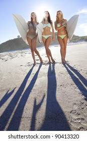 Three beautiful young women surfer girls in bikinis with white surfboards at a beach