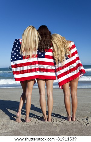 2cf39bf10d68 Three beautiful young women wearing bikinis and wrapped in American flags  on a sunny beach
