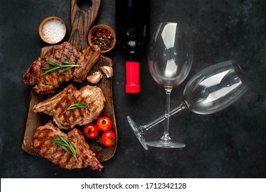 three beef steaks with grilled spices, a bottle of red wine and glasses on a stone background