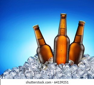 Three beer bottles getting cool in ice cubes. Isolated on a blue. File contains clipping path.