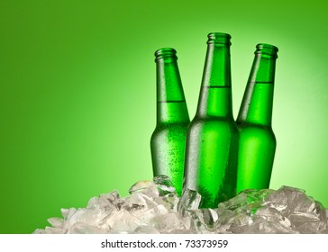 Three beer bottles getting cool in ice cubes. Isolated on a green.