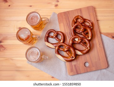 Three beer mugs and soft salted pretzels on wooden cutting board. Top view.