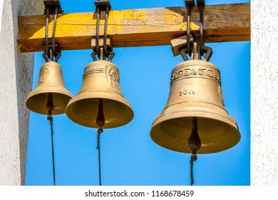 Three bells different sizes on the bell tower of the Orthodox church on the background of the blue sky on a sunny day