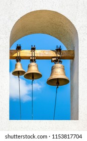 Three bells on the bell tower of the Orthodox church on the background of the blue sky on a sunny day