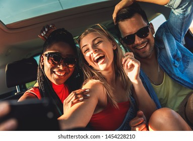 Three best friends enjoying traveling in the car, sitting in rear seat and having lots of fun making selfie on a road trip.