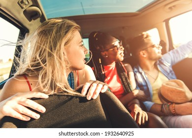 Three best friends enjoying traveling in the car, sitting in rear seat and having lots of fun on a road trip.