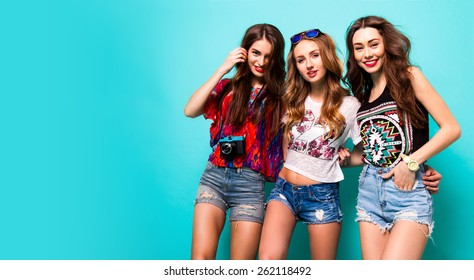 Three best friends posing in studio, wearing summer style outfit and jeans shorts  against blue background. Girls smiling and having fun.